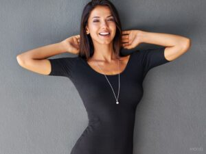 Brunette in Tight Black Dress Wearing Long Silver Necklace